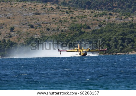 GREBASTICA, CROATIA - JULY 7: Canader takes water to put out fire on July 7, 2010 in Grebastica, Croatia