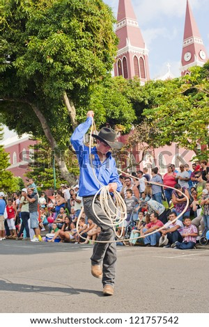 GRECIA, COSTA RICA-CIRCA DECEMBER 9:Cowboy performs rope tricks in Grecia circa December 9, 2012. Each December, El Tope is a rodeo style event with cowboys performing rope and riding tricks. - stock photo