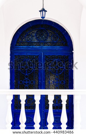 Greece, arched door with ornaments, painted in blue on a white wall. Collon and in the foreground. - stock photo