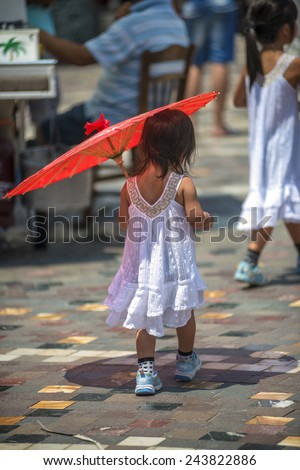 GREECE, ATHENS - JULY 19, 2014: Chinese tourist girls walking with an umbrella. - stock photo