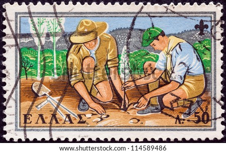 "GREECE - CIRCA 1960: A stamp printed in Greece from the ""50th anniversary of Greek Boy Scout Movement"" issue shows Scouts planting a tree, circa 1960. - stock photo"