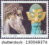 GREECE - CIRCA 2007: A stamp printed in Greece issued for the Cultural Year of Greece in China shows Zeus of Artemision statue and bronze head sculpture with golden mask, Shang dynasty, circa 2007. - stock photo