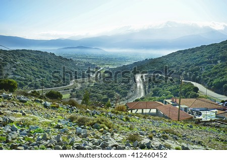 Greece, Crete, Ambelos pass with mountain road to Lassithi plateau and snowy Ida range behind