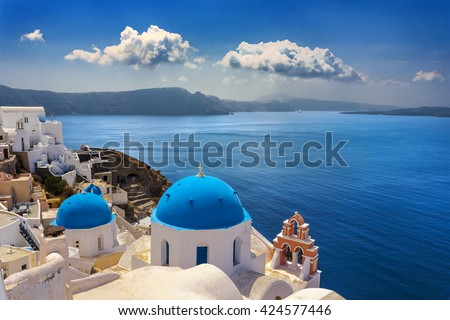 Greece. Cyclades Islands - Santorini (Thira). Oia town with typical Cycladic architecture - painted blue cupolas and white walls of houses. The Anastasis Church - stock photo