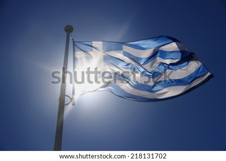 Greece flag on blue sky, backlit subject, contre-jour - stock photo