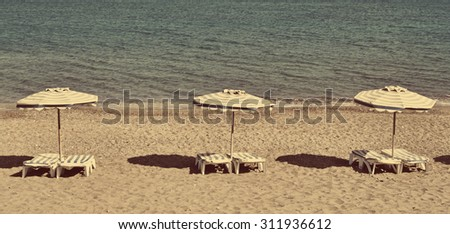 Greece. Kos island. Chairs and umbrellas on the Kefalos beach. In instagram style filtered - stock photo