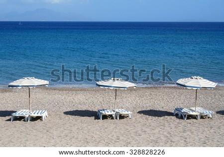 Greece. Kos island. Kefalos beach. Chairs and umbrellas on the beach  - stock photo
