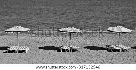Greece. Kos island. Kefalos beach. Chairs and umbrellas on the beach. In black and white  - stock photo