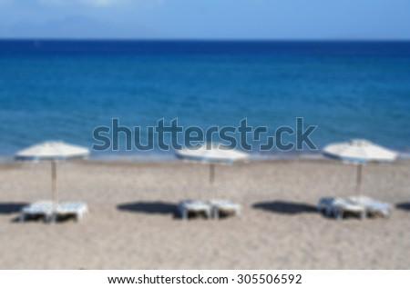 Greece. Kos island. Kefalos beach. Chairs and umbrellas on the beach. In blur style    - stock photo