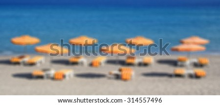 Greece. Kos island. Kefalos beach. Orange chairs and umbrellas on the beach. In blur style   - stock photo