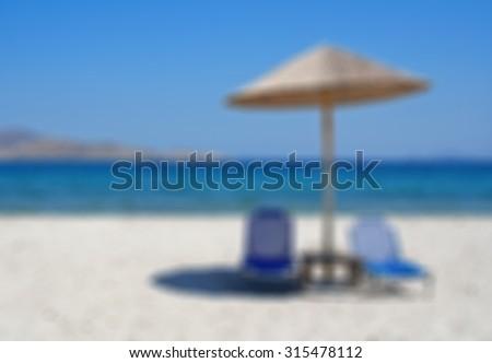 Greece. Kos island. Tigaki beach.Two chairs and umbrella on the white sand beach. In blur style   - stock photo