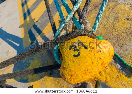 Greece Piraeus,Yellow rusty metal bollard and ship rope harbor at sunny day with ships in background