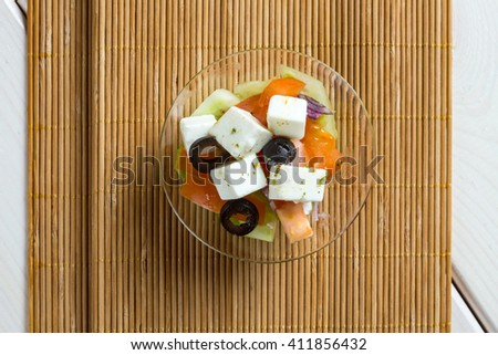 Greece style salad in glass bowl on wood mat - stock photo
