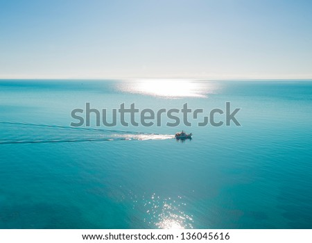 Greece Syros, wide view of sea with sun reflecting on seawater and boats passing by, Syros is a Greek islands in Cyclades - stock photo