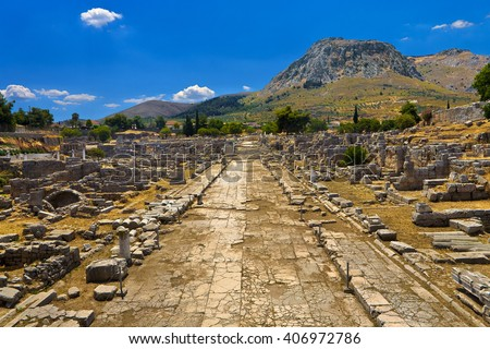 Greece. The Archaeological Site of Ancient Corinth. Lechaion Road (cardo maximus) paved with limestone slabs and remains of monuments. There is Acrocorinth with citadel formed on the top of rock - stock photo