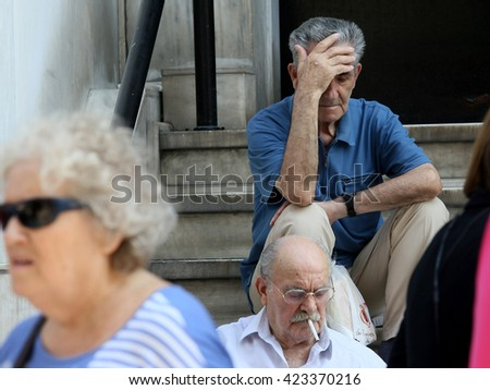 GREECE, Thessaloniki JUNE 28, 2015 Citizens line up to use an automated teller machine (ATM) outside a closed bank. Cash machines ran dry after Greeks rushed to withdraw their savings from the banks
