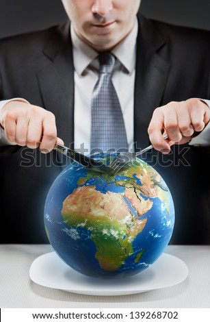 Greedy businessman cutting planet Earth. Elements of this image furnished by NASA