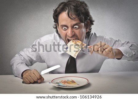 Greedy businessman eating banknotes from a dish - stock photo