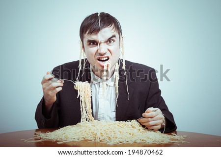 Greedy consumerism concept. Nasty businessman eating pasta on the table.