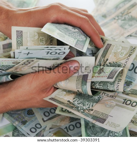 Greedy hand grabs money lot of polish banknotes - stock photo