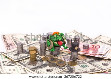 Greedy Leprechaun on the pile of money with two euro coin - finance concept isolated on white - stock photo