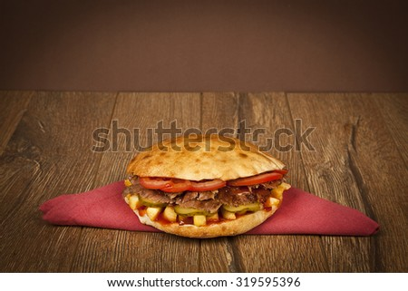 Greek and Turkish gyros stuffed sandwich with roasted meat salad onions fried potatoes and tzatziki saucer olled into a pita on a plate Patso with lamb doner kebab - stock photo