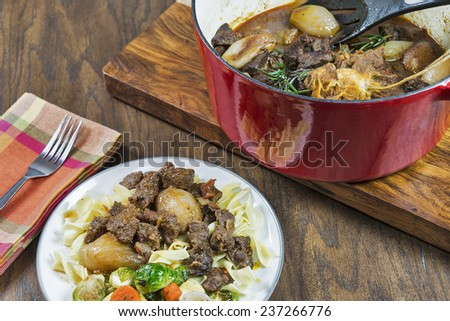 Greek Beef Stifado served over egg noodles with roasted vegetables - stock photo