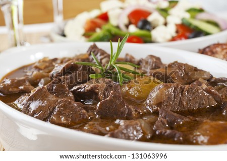 Greek dish Stifado, made with lamb and served with Greek salad. Can also be made with beef or game. - stock photo