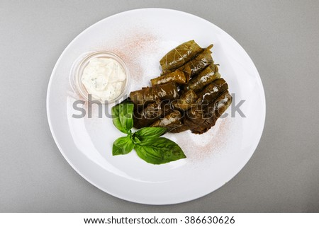 Greek dolma in grape leaves with meat served basil. Top view - stock photo