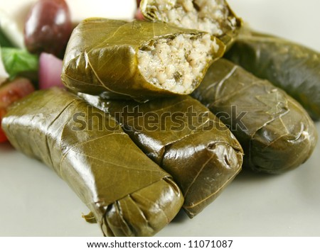 Greek dolmas wrapped with vine leaves and rice with salad.