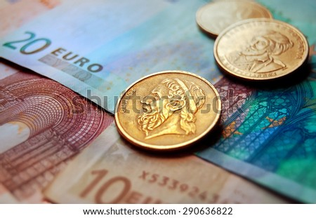 Greek drachma coins on Euro banknotes. Selective focus. - stock photo