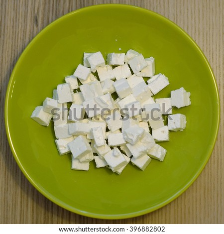 Greek feta cheese cubes on the plate. Isolated. - stock photo