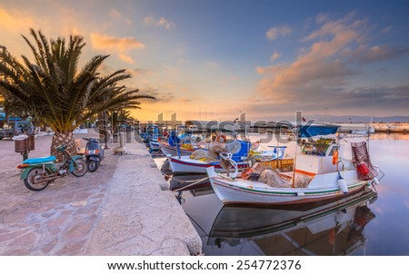 Greek fishing harbor scene with boats, palm trees and scooters at sunrise on a beautiful tranquil summer day in july - stock photo