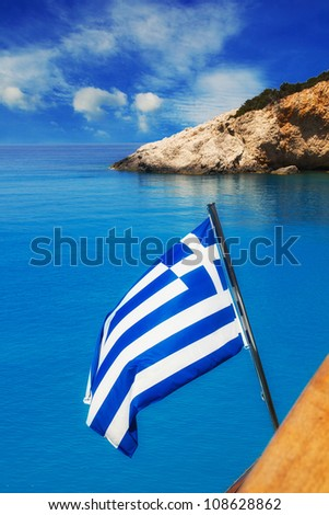 Greek flag on a cruise ship with the famous Porto Katsiki beach in the background - stock photo