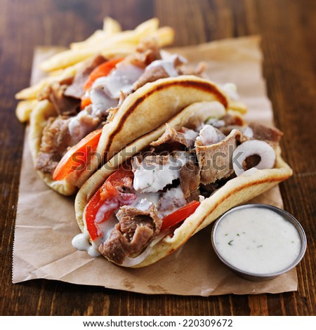 greek gyros with tzatziki sauce and fries on parchment - stock photo