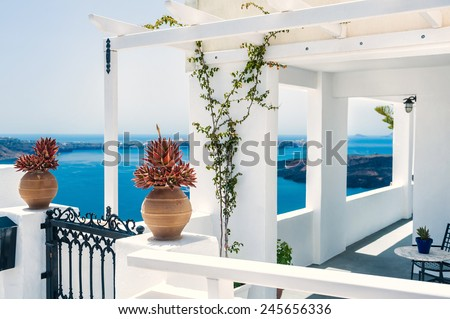 Greek house with terrace and sea view. White architecture on Santorini island, Greece.  Beautiful summer landscape. Small depth of sharpness - stock photo