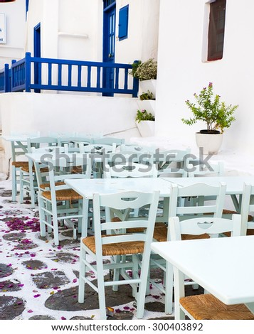 Greek island restaurants with colorful tables and chairs.