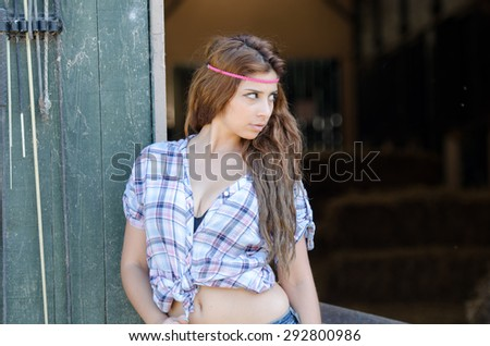Greek model young woman in farm with curly hair and plaid shirt tied at the waist, leaning against the door - stock photo