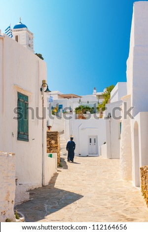 Greek Orthodox priest walking in an alleyway on the island of Sifnos - stock photo