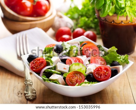 greek salad in a bowl on wooden table - stock photo