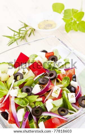Greek salad in bowl close up, olive oil dressing and fresh herbs in background. - stock photo