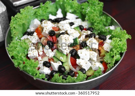 Greek salad in bowl on a table - stock photo