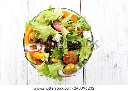 Greek salad in glass dish on color wooden table background - stock photo