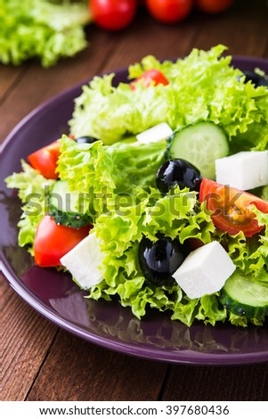 Greek salad (lettuce, tomatoes, feta cheese, cucumbers, black olives) on dark wooden background close up. Healthy food. - stock photo