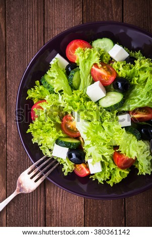 Greek salad (lettuce, tomatoes, feta cheese, cucumbers, black olives) on dark wooden background top view. Healthy food. - stock photo