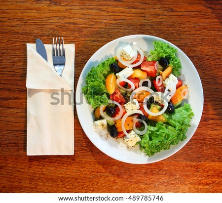 Greek salad (lettuce, tomatoes, feta cheese, cucumbers, black olives) on dark wooden background top view. Space for text. Healthy food