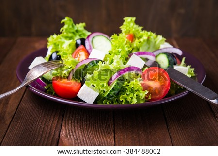 Greek salad (lettuce, tomatoes, feta cheese, cucumbers, black olives, purple onion) on dark wooden background close up. Healthy food. - stock photo
