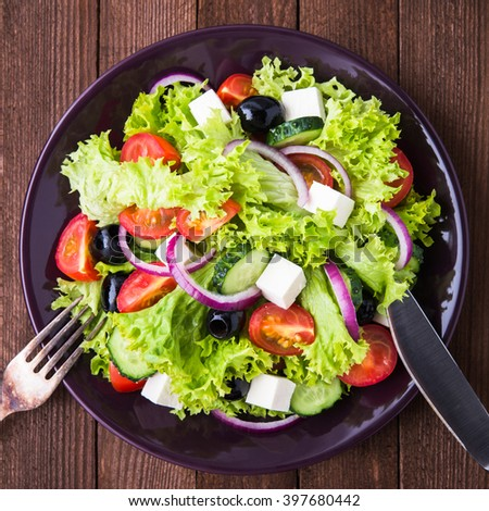 Greek salad (lettuce, tomatoes, feta cheese, cucumbers, black olives, purple onion) on dark wooden background top view. Healthy food. - stock photo