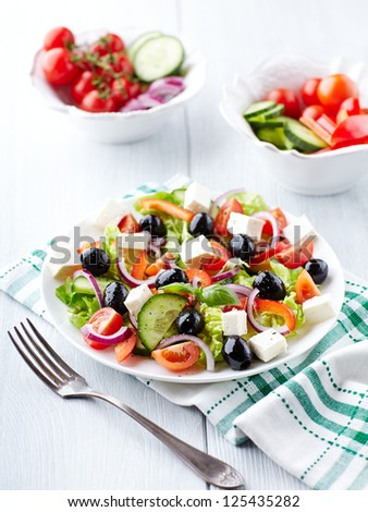 Greek Salad on Kitchen Table - stock photo