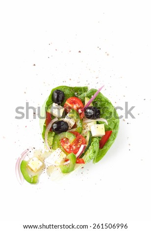 Greek salad on white background from above. Feta cheese, cherry tomatoes, onion, cucumber, olives, lettuce and red pepper. Layout with free text space.